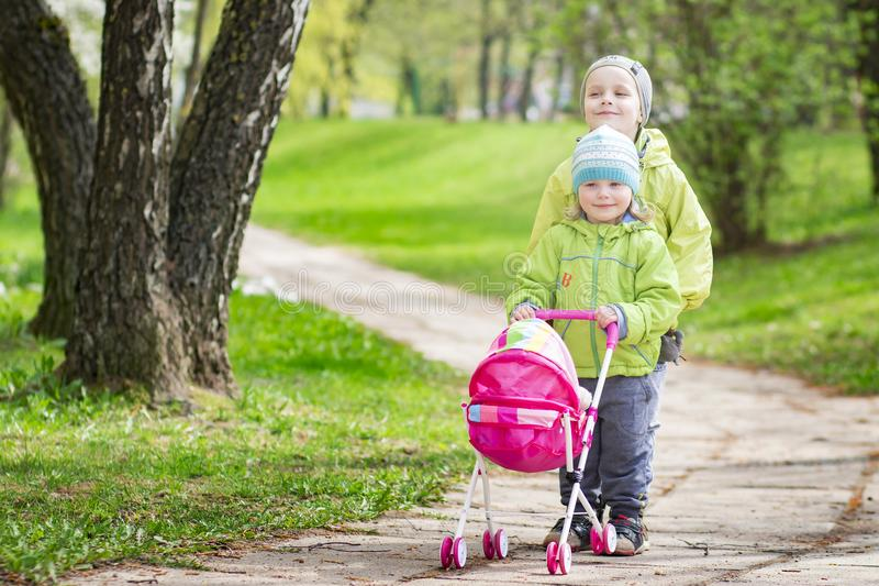 Little children play in yard with children`s toy doll for dolls. boy and girl play game of children playing stroller in courtyard stock image
