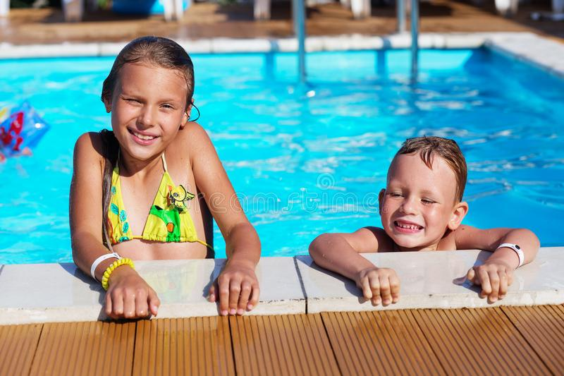 Little children playing and having fun in swimming pool with air. Mattress. Kids playing in water. Swimming concept. Boy and girl swim in resort pool during royalty free stock photo