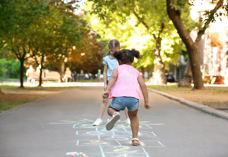 Little children playing hopscotch drawn with colorful chalk stock photos
