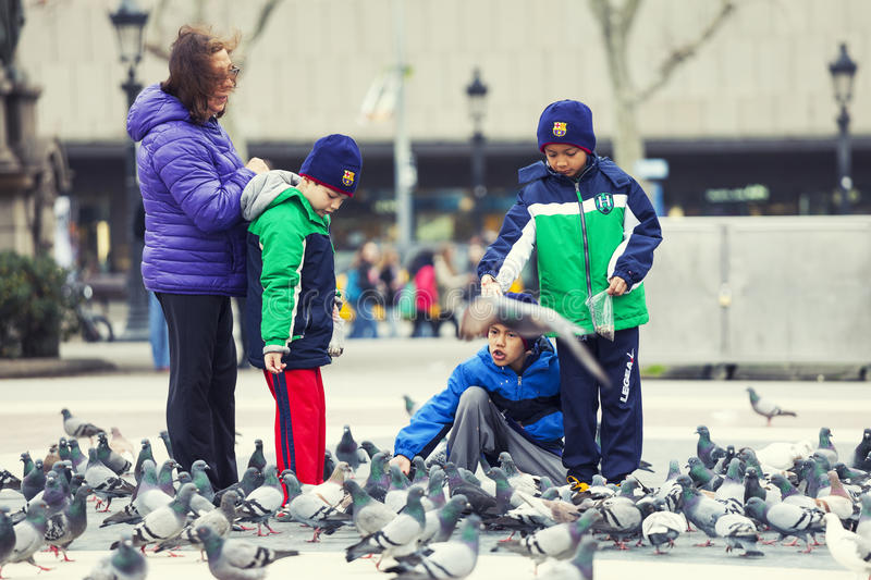 Little children playing with pigeons. Kids in Barcelona, Spain stock image