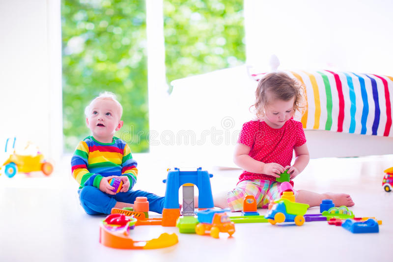 Little children playing with toy cars. Two happy children playing with toy cars, cute curly toddler girl and a funny baby boy, brosther and sister, sitting on stock images