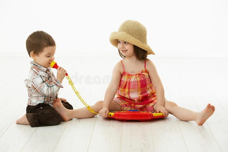 Little children playing with toy instrument. Happy kids playing on toy music instrument, little boy singing to microphone over white background royalty free stock photos