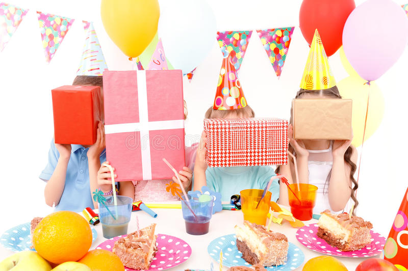 Little children posing with birthday presents. Hide and seek. Group of little cheerful kids sitting at table during birthday party and covering their faces with royalty free stock image