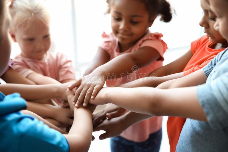 Little children putting their hands together, closeup. Unity concept royalty free stock images