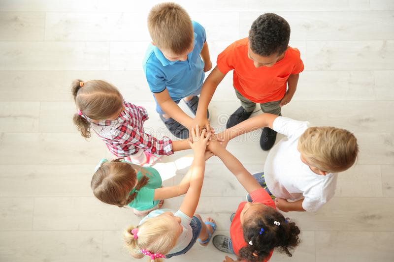 Little children putting their hands together indoors. Top view. Unity concept stock photography