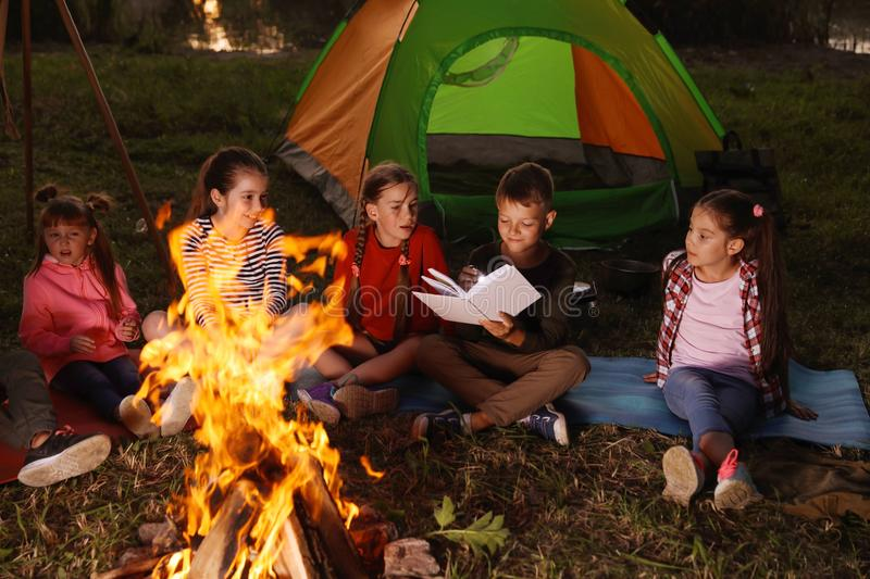 Little children reading book with flashlight outdoors stock photos