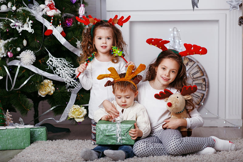 Little children in reindeer antlers. In anticipation of new year and Christmas. Three little siblings opening christmas gifts. Kids in comfortable home clothes royalty free stock photography