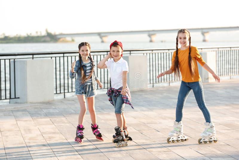 Little children roller skating stock photos