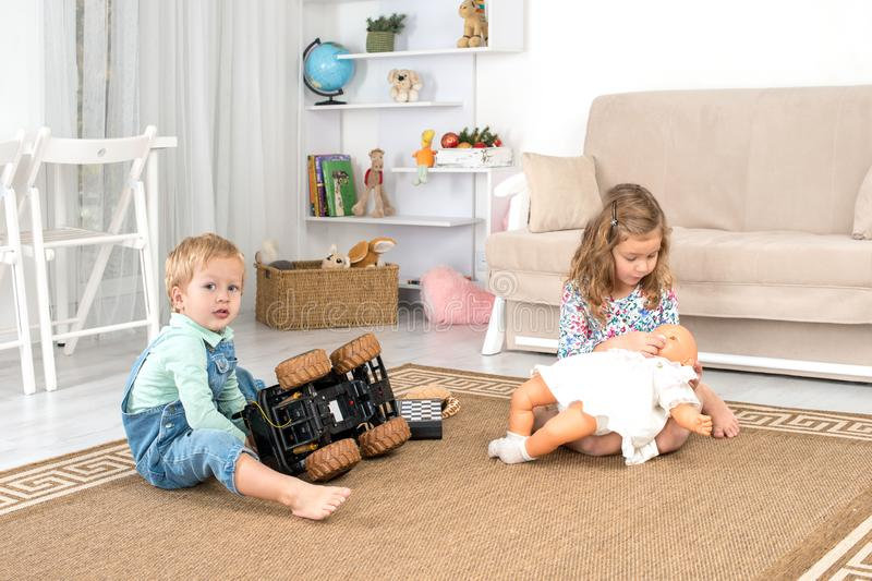 Little children sit on the floor on a rug in the room at home and play with a toy car and a doll. Little children, a boy and a girl, sit on the floor on a rug in royalty free stock images