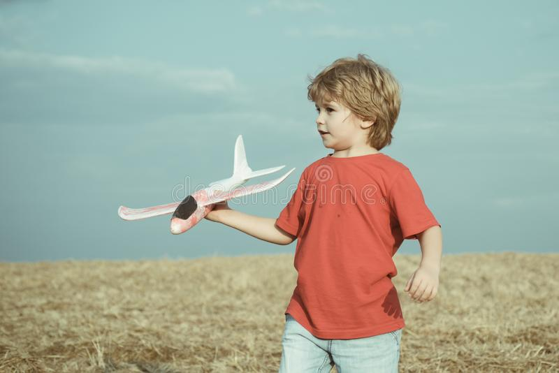 Little children with toy airplane in a field at sunset. Success and child leader concept. Boy dreams of becoming a pilot stock photo
