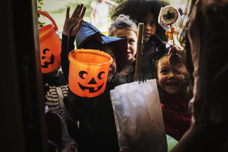 Little children trick or treating on Halloween stock images