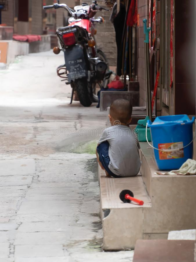Little Chinese boy playing on a narrow alley of Xiaozhou Village, China royalty free stock photo