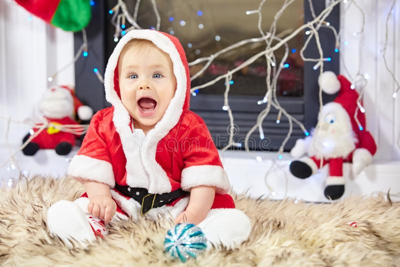 Little Christmas Baby in Santa costume. Child holding Blue Ball near Holiday Lights background. royalty free stock photos