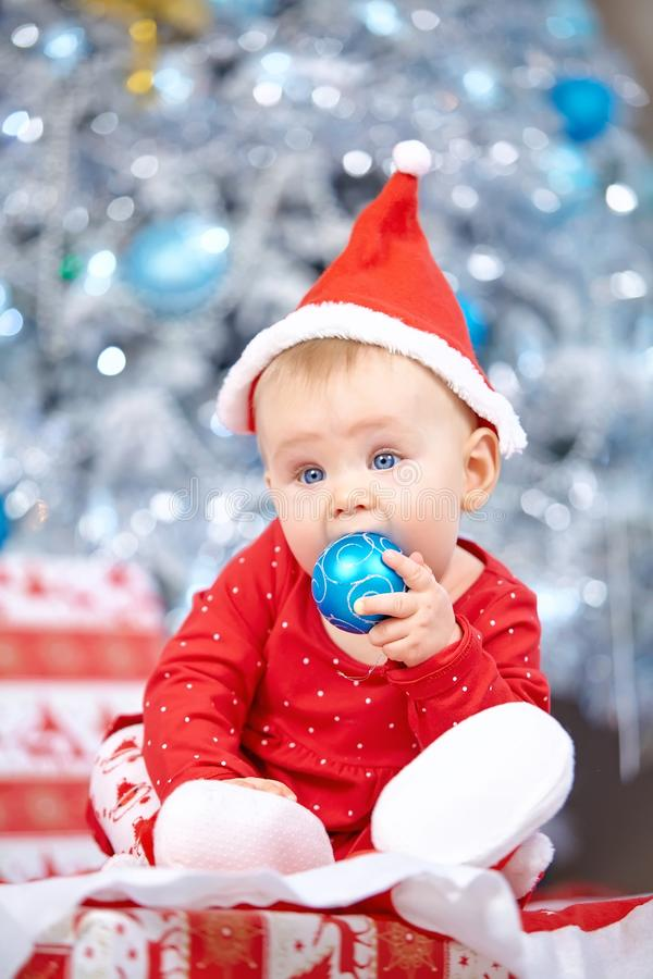 Little Christmas Baby in Santa costume. Child holding Blue Ball near Holiday Lights background. stock images