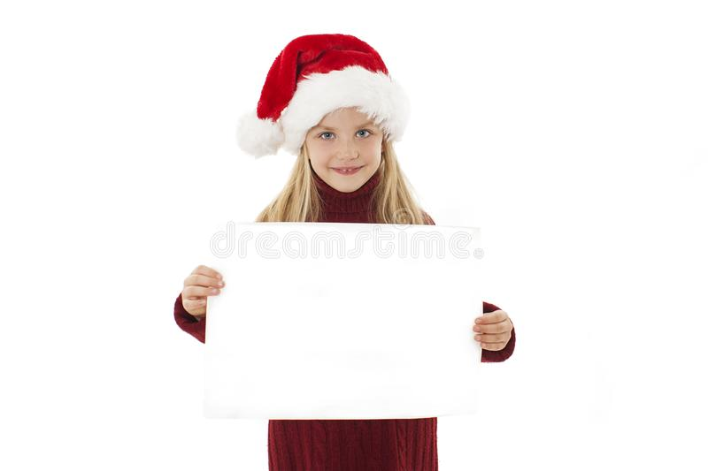 Little Christmas girl presenting. Adorable little girl holding a blank paper. stock image