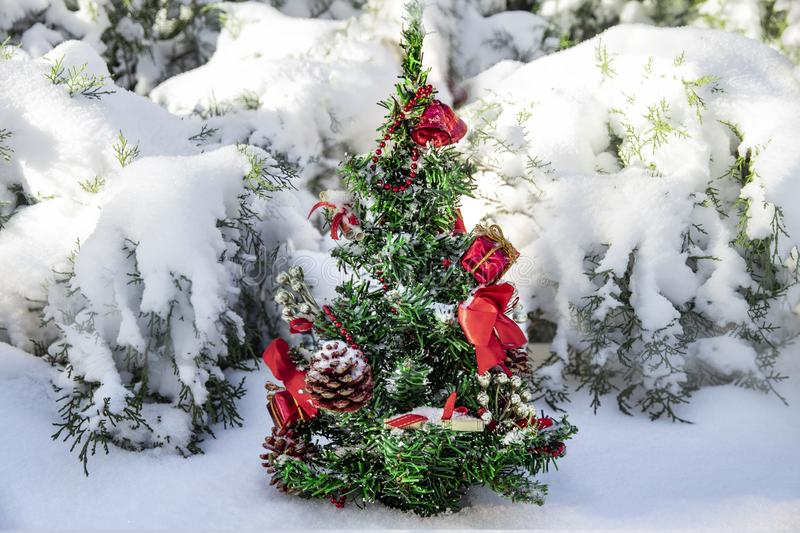 Little Christmas tree with toys in a snowy forest royalty free stock images