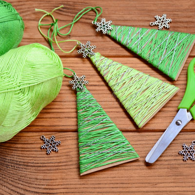 Little Christmas trees are made of carton, cotton yarn and decorated with small metal snowflakes. Easy and cheap Christmas crafts. Mery Christmas. Christmas tree stock photography