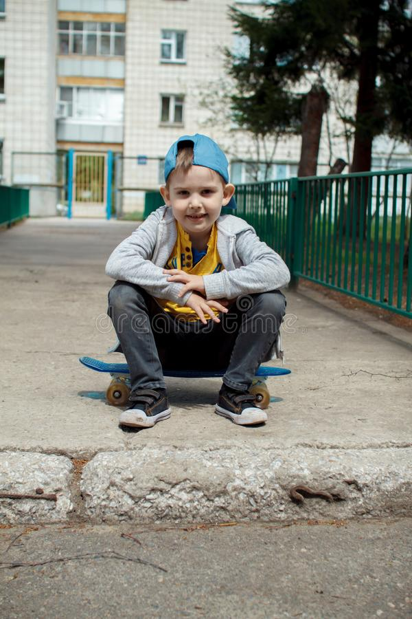 Little city boy with a skateboard. Young guy in a cap sits. Urban style. City kids. Kid`s having fun stock photo