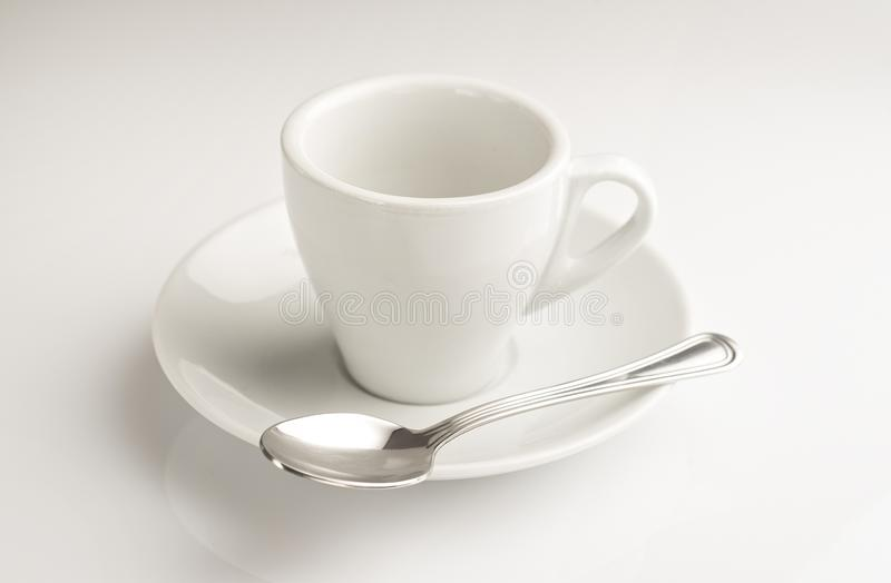 A little coffee cup with teaspoon in a white background royalty free stock photography