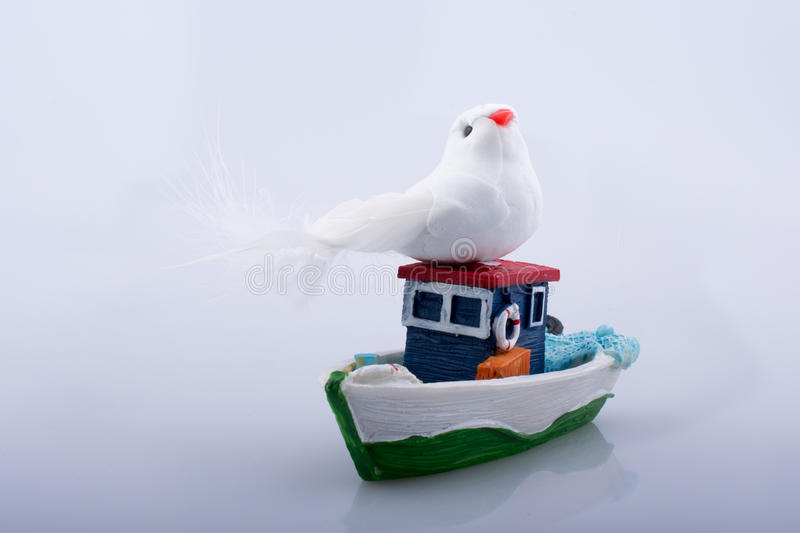 Little colorful model boat with a fake bird. On white background stock photography