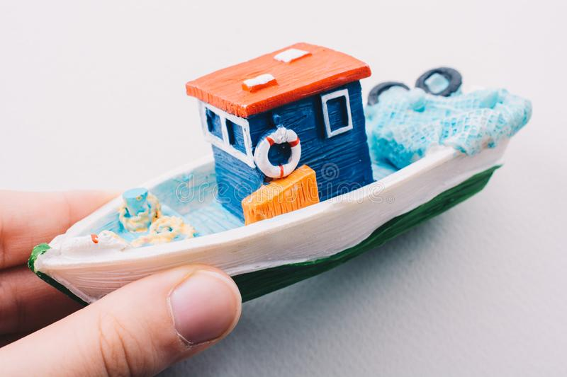 Little colorful model fishing boat in hand. On white stock photography