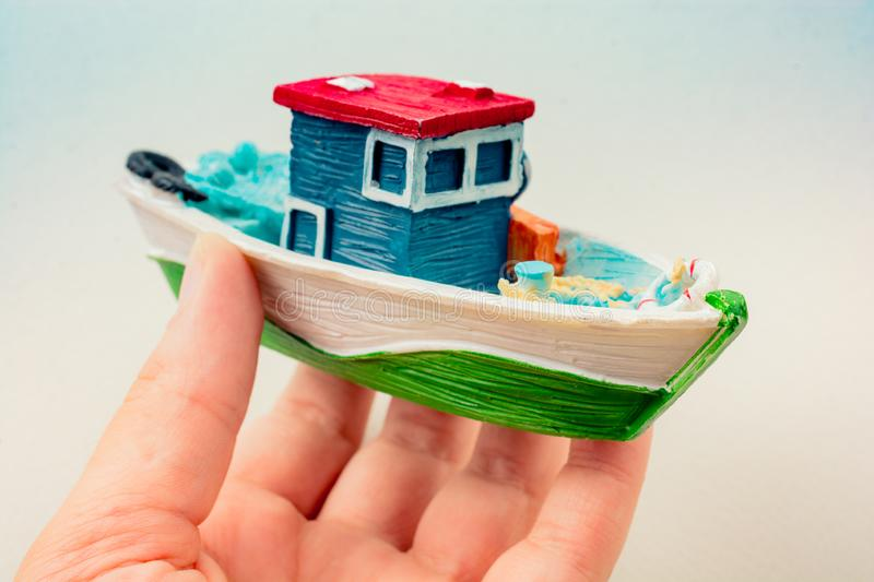 Little colorful model fishing boat in hand. On white royalty free stock photography