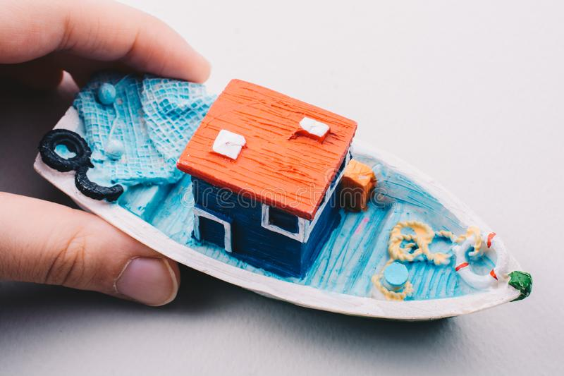 Little colorful model fishing boat in hand. On white royalty free stock image