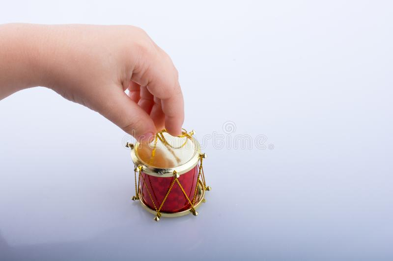 Little colorful toy drum  in hand. Hand holding a  toy drum on a white background royalty free stock photos