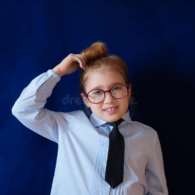 Little confused schoolgirl scratching head royalty free stock photography