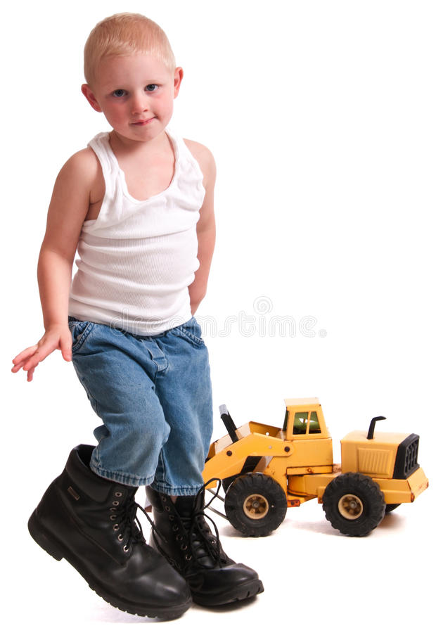 Little Construction Worker. Cute little blonde boy wearing his daddy's boots while playing with a toy front loader royalty free stock photography