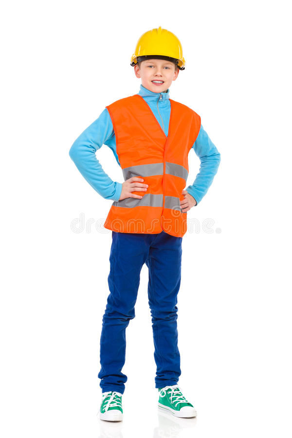 Little construction worker. Young boy posing in yellow hard hat and orange reflective vest. Full length studio shot isolated on white stock photography
