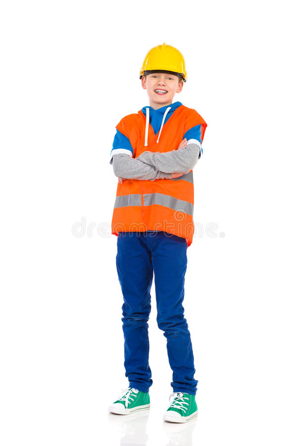 Little construction worker. Young boy in yellow hard hat and orange reflective vest posing with arms crossed. Full length studio shot isolated on white stock image
