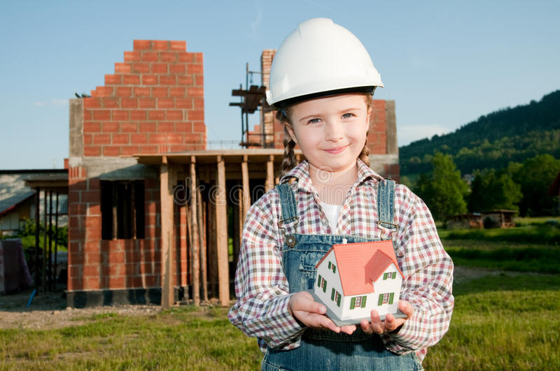 Little constructor. Little girl with house model and house under construction royalty free stock photos
