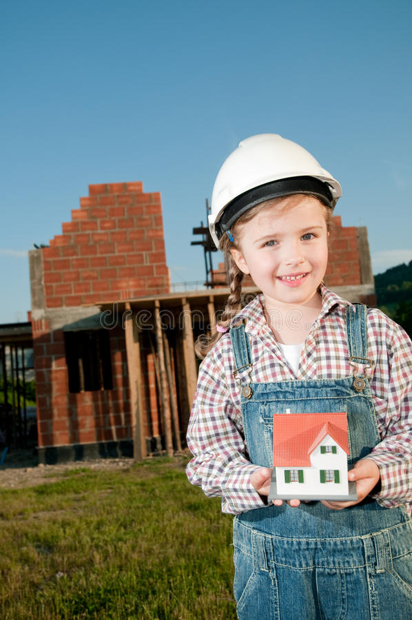 Little constructor. Little girl with house model and house under construction stock photography