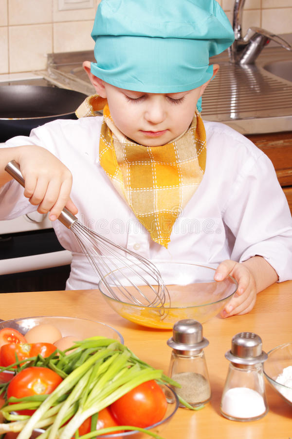 Little cook beating up eggs royalty free stock images