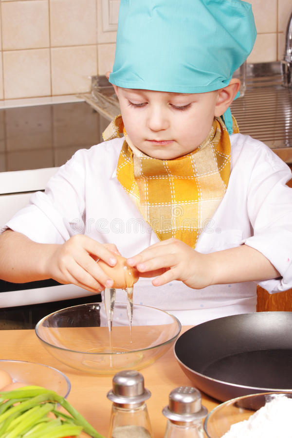 Little cook breaking egg. Little cook boy breaking egg and pouring it into glass bowl stock photos