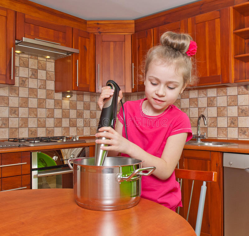 Little cook. Cute little girl uses a blender in the kitchen royalty free stock photo