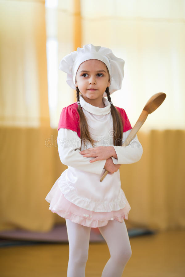 Little cook. Little girl wearing chef's hat with big wooden spoon stock photo