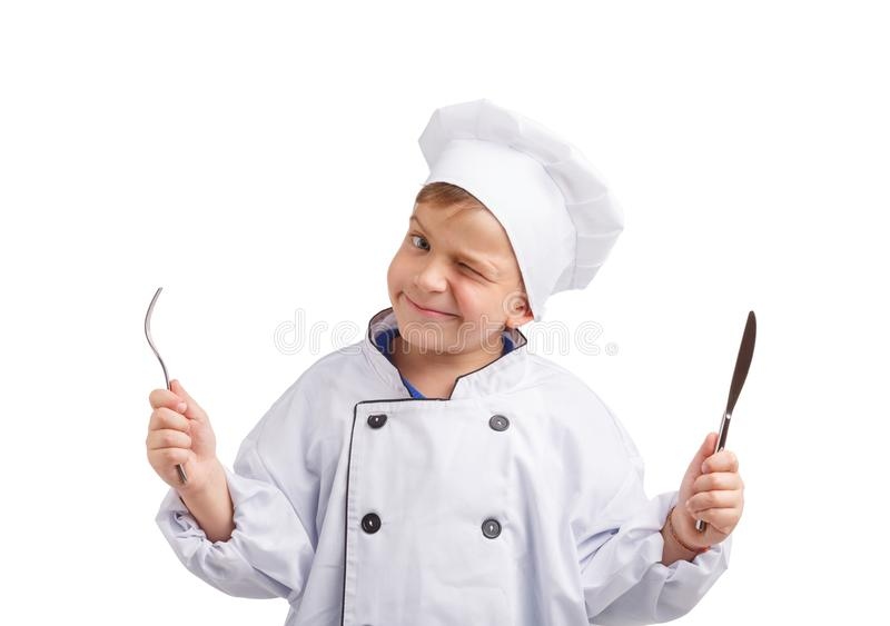Little cook with fork and knife in hands on a white isolated background. Little cook in shape with fork and knife in hands winking one eye on white isolated stock images