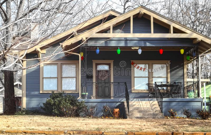 Little cottage with giant Christmas lights on porch and Merry Christmas acros window on bleak winter day royalty free stock photo