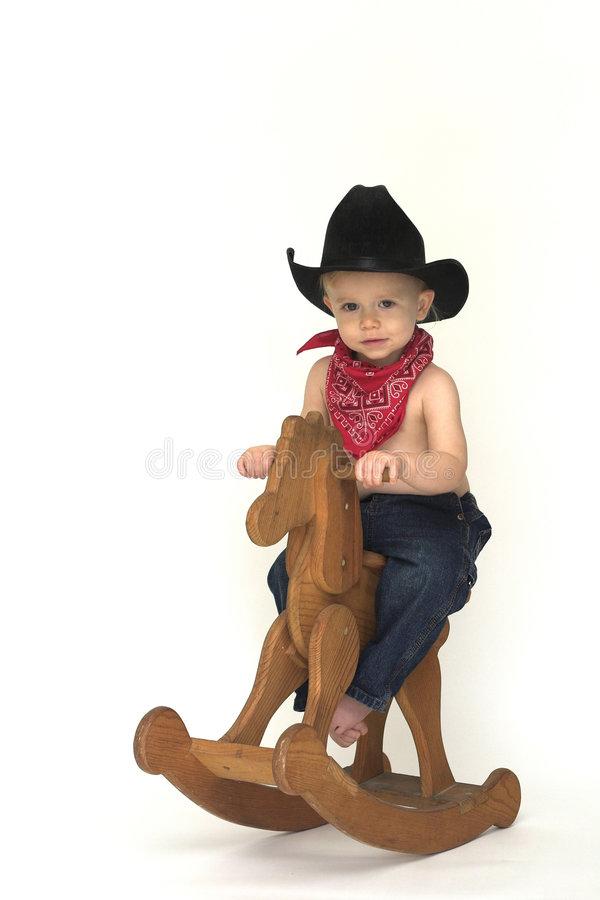 Little Cowboy. Image of cute toddler wearing a black cowboy hat, red bandanna and jeans, riding a wooden rocking horse royalty free stock photos