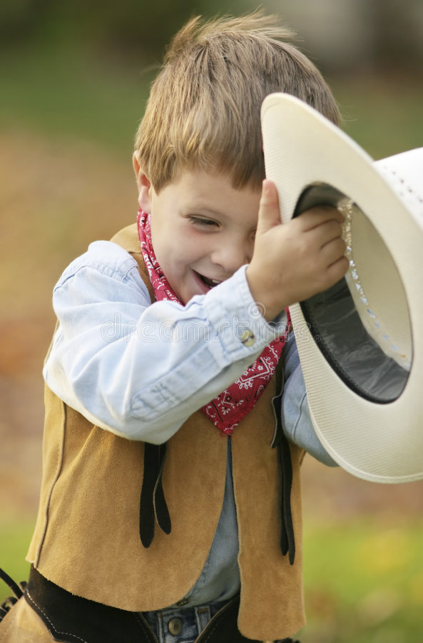 Little cowboy. A little cowboy holding on to his hat in the wind royalty free stock images