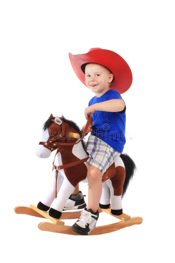 Little cowboy on a horse. Little cowboy on a rocking horse, isolated on white stock image