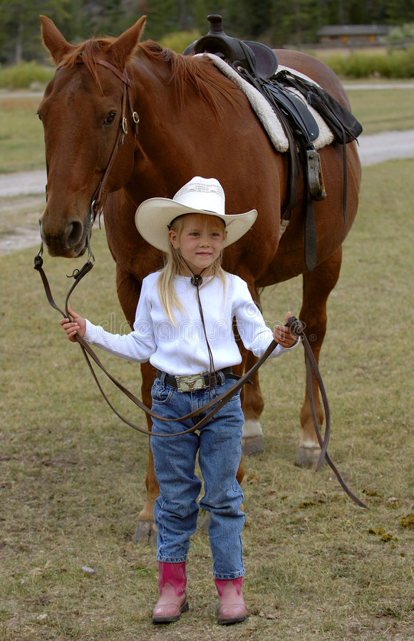 Little Cowgirl Holding Chestnut/Sorrel Horse