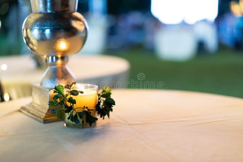 Little cozy candle on the white circle table with blur background royalty free stock image