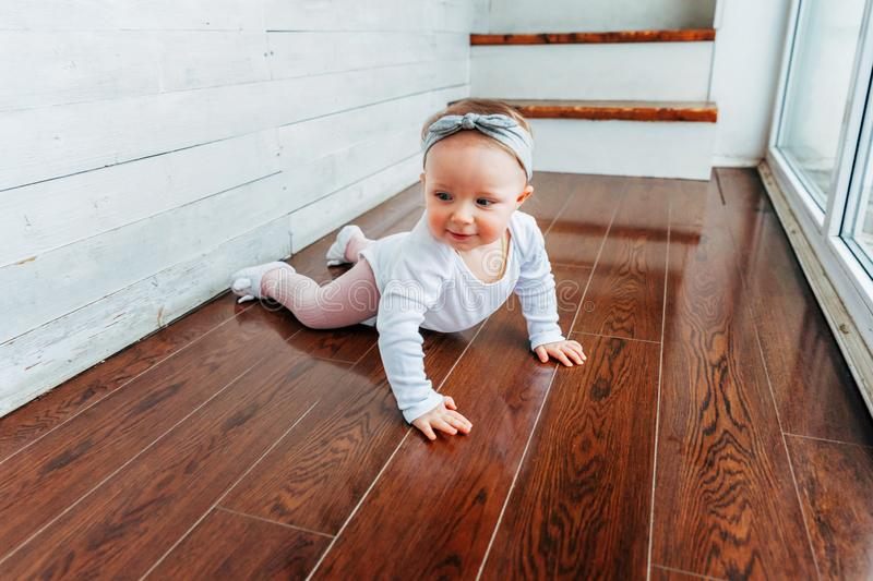 Little crawling baby girl one year old siting on floor in bright light living room near window smiling and laughing royalty free stock image