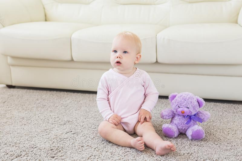 Little crawling baby girl one year old sitting on floor in bright light living room smiling and laughing. Happy toddler royalty free stock photography