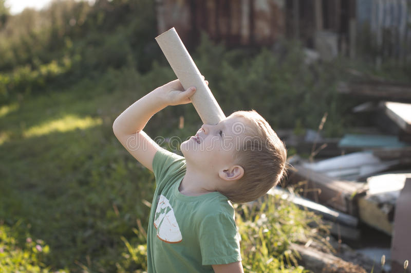Little curious explorer. Boy looking at skies through the cardboard spyglass stock photos