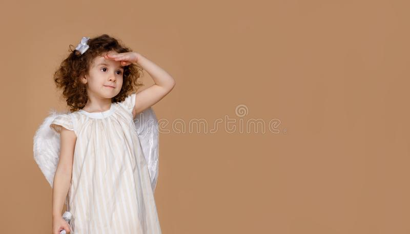 Little curly Angel girl with wings and dress seeking at side. beige at the background. Child with angelic character. royalty free stock photo