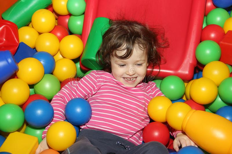 Little curly cute smile girl plays in balls for a dry pool. Play room. Happiness royalty free stock photos